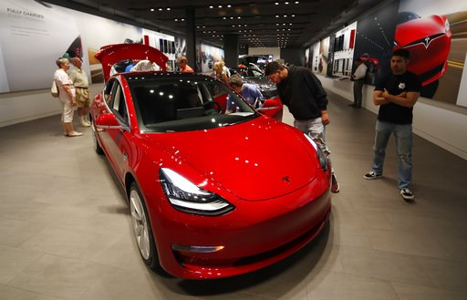 (AP Photo/David Zalubowski). In this Friday, July 6, 2018, photograph, prospective customers confer with sales associates as a Model 3 sits on display in a Tesla showroom in the Cherry Creek Mall in Denver.  The Insurance Institute for Highway Safety, ...