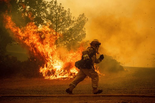 (AP Photo/Noah Berger, File). FILE - In this Tuesday, July 31, 2018, file photo, a firefighter runs while trying to save a home as a wildfire tears through Lakeport, Calif. The residence eventually burned. Authorities say a rapidly expanding Northern C...