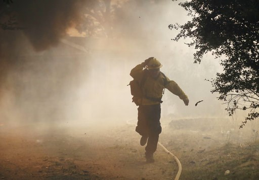 (AP Photo/Marcio Jose Sanchez, File). FILE - In this Monday, July 30, 2018, file photo, a firefighter runs from a burning structure, in Finley, Calif. Authorities say a rapidly expanding Northern California wildfire burning over an area the size of Los...