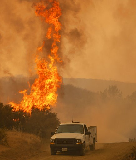 (AP Photo/Josh Edelson, File). FILE - In this Sunday, Aug. 5, 2018, file photo, a truck passes by flames during the Ranch Fire in Clearlake Oaks, Calif. Authorities say a rapidly expanding Northern California wildfire burning over an area the size of L...