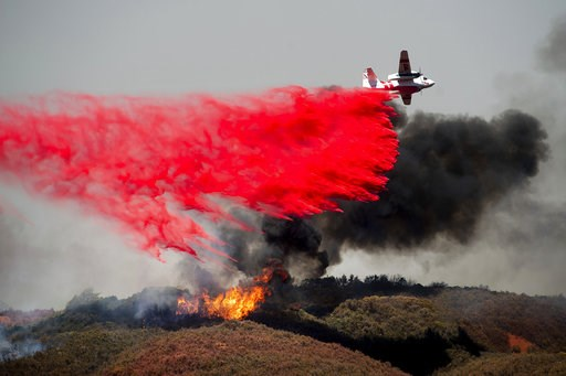 (AP Photo/Noah Berger, File). FILE - In this Monday, July 30, 2018, file photo, an air tanker drops retardant on a wildfire burning near Lakeport, Calif. Authorities say a rapidly expanding Northern California wildfire burning over an area the size of ...