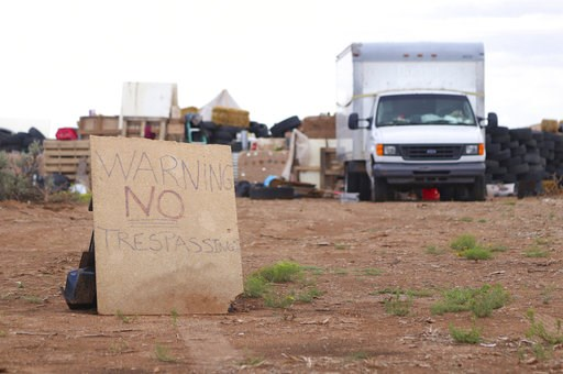 """(Jesse Moya/The Taos News via AP). This Aug. 5, 2018 photo shows a """"no trespassing"""" sign outside the location where people camped near Amalia, N.M. Three women believed to be the mothers of 11 children found hungry and living in a filthy makeshift comp..."""