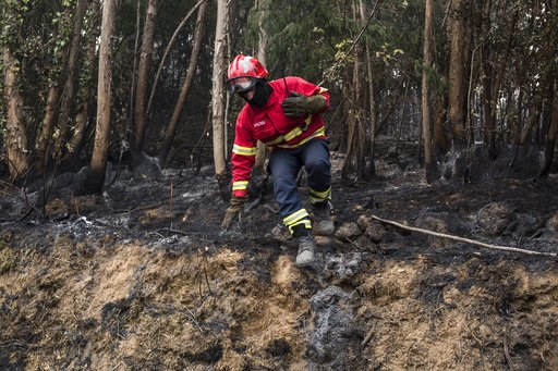 (AP Photo/Javier Fergo). A firefighter jumps off a small mound while working on a fire near the village of Monchique, in southern Portugal's Algarve region, Monday, Aug. 6, 2018. Emergency services in Portugal say they are still fighting a major wildfi...