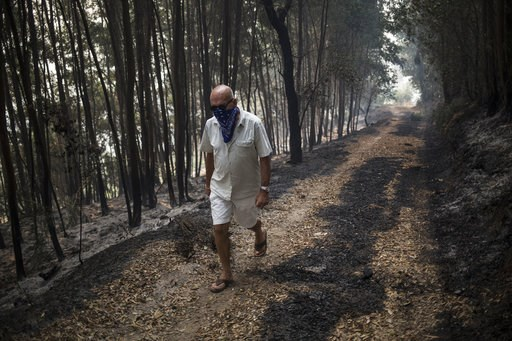 (AP Photo/Javier Fergo). A man walks a path wearing a bandana as an improvised mask outside the village of Monchique, in southern Portugal's Algarve region, Monday, Aug. 6, 2018. Emergency services in Portugal say they are still fighting a major wildfi...