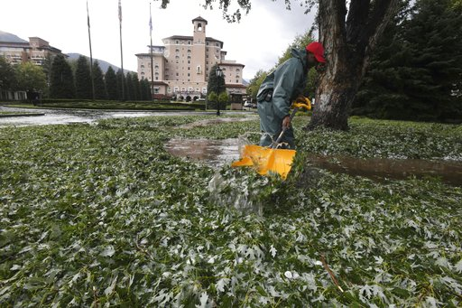 (Jerilee Bennett/The Gazette via AP). The Broadmoor Hotel employee Carlton Burton shovels leaves and hail after a storm Monday, Aug. 6, 2018, damaged trees, vehicles and buildings in the Colorado Springs, Colo., area.