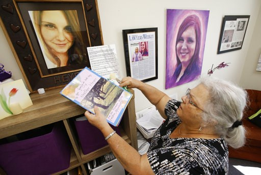"""(AP Photo/Steve Helber). In this Monday, Aug. 6, 2018 photo, Susan Bro, mother of Heather Heyer, who was killed during the Unite the Right rally last year, looks over memorabilia in her office in Charlottesville, Va. """"I just would like people to focus ..."""