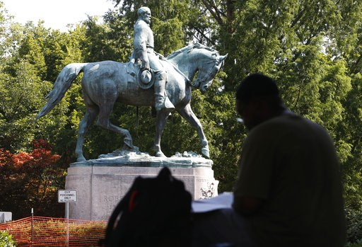 (AP Photo/Steve Helber). In this Monday, Aug. 6, 2018, photo, a visitor eats lunch in front of a statue of Robert E. Lee that is surrounded by fencing and a No Trespassing sign in Charlottesville, Va., at the park that was the focus of the Unite the Ri...
