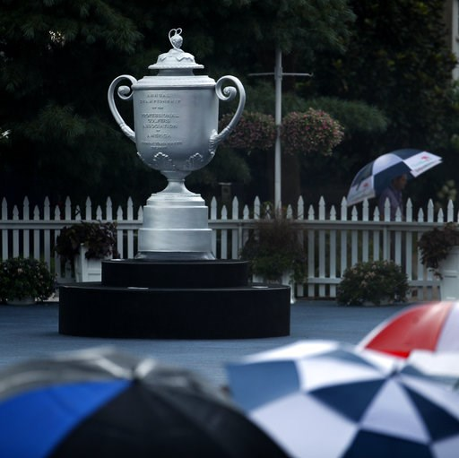 (AP Photo/Charlie Riedel). Fans shelter under umbrellas near a replica of the Wanamaker Trophy during a rain delay during practice at the PGA Championship golf tournament Tuesday, Aug. 7, 2018, at Bellerive Country Club in Saint Louis.