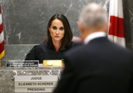 (AP Photo/Wilfredo Lee, Pool). Judge Elizabeth Scherer, rear, listens to chief assistant state attorney Jeff Marcus during hearing for school shooting suspect Nikolas Cruz in a Broward County courtroom in Fort Lauderdale, Fla., Friday, Aug. 3, 2018. At...