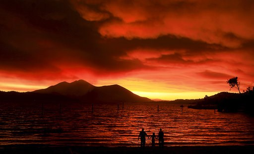 (Kent Porter/The Press Democrat via AP). Evacuees from Lucerne, from left, Ken Bennett with Ember Reynolds, 8, and Lisa Reynolds watch the sunset as smoke from the Ranch Fire rises into the sky at Austin Park Beach in California's Clearlake with Mount ...