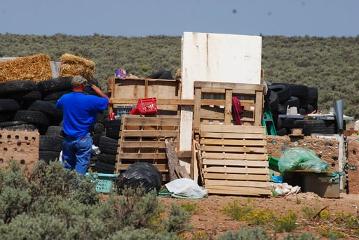 (AP Photo/Morgan Lee). Taos County Solid Waste Department Director Edward Martinez surveys property conditions at a disheveled living compound at Amalia, N.M., Tuesday, Aug. 7, 2018. The investigation into a group of starving children found in the dese...
