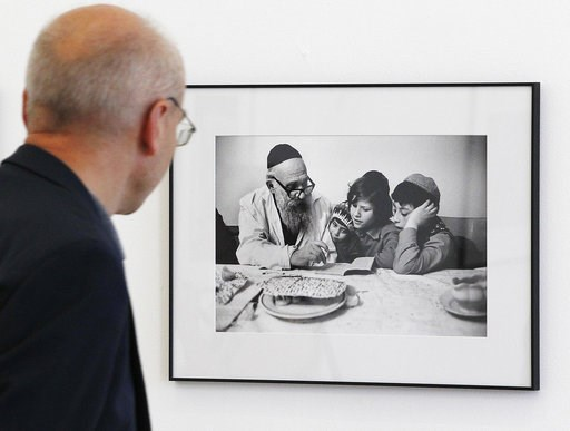 (AP Photo/Czarek Sokolowski). A visitor looks at  a photograph documenting Jewish life in Poland from the 1970s, in Warsaw, Poland, Wednesday, Aug. 8, 2018. A new photo exhibition in Warsaw documents more than 40 years of Jewish life in Poland _ from t...