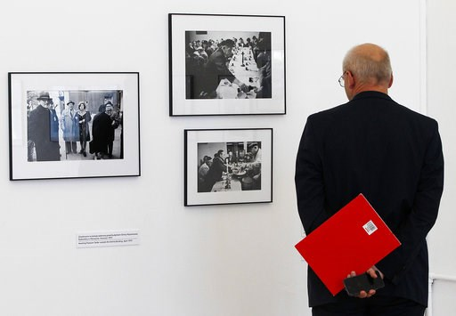 (AP Photo/Czarek Sokolowski). A visitor looks at photographs documenting Jewish life in Poland from the 1970s, when it seemed Jewish life was on the brink of extinction, to a Jewish revival underway in present day, Wednesday, Aug. 8, 2018 in Warsaw, Po...