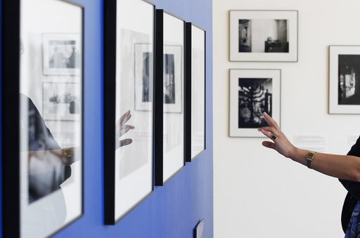 (AP Photo/Czarek Sokolowski). A visitor points at one of the photographs on display documenting Jewish life in Poland from the 1970s, in Warsaw, Poland, Wednesday, Aug. 8, 2018. A new photo exhibition in Warsaw documents more than 40 years of Jewish li...