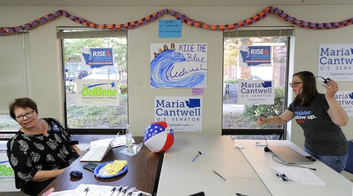 "(AP Photo/Ted S. Warren). Campaign volunteers work at a table below a sign that reads ""Ride the Blue Wave,"" during a gathering at a combined campaign headquarters for Democrats running for office in Redmond, Wash. on the night of Washington state's pri..."