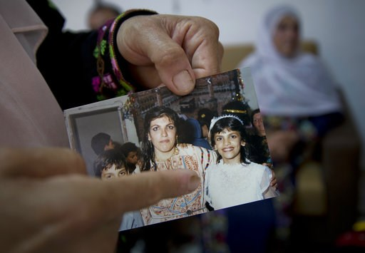 (AP Photo/Nasser Nasser). In this Wednesday, Aug. 8, 2018 photo, Fadwa Tlaib, an aunt of Rashida Tlaib points to a young Rashida in a 1987 picture with her mother Fatima and brother Nader, at the family house, in the West Bank village of Beit Ur al-Foq...
