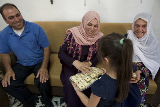 (AP Photo/Nasser Nasser). In this Wednesday, Aug. 8, 2018 photo, a Palestinian girl offers sweets to family members of Rashida Tlaib -- aunt Fadwa, center, grandmother Muftiyeh, right and uncle Bassam -- as they celebrate Rashida's U.S. election victor...
