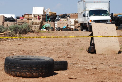 (AP Photo/Morgan Lee). CORRECTS BYLINE TO MORGAN LEE INSTEAD OF LEE MORGAN - Police tape restricts access to a disheveled living compound in Amalia, N.M., on Tuesday, Aug. 7, 2018. A New Mexico sheriff said searchers have found the remains of a boy at ...