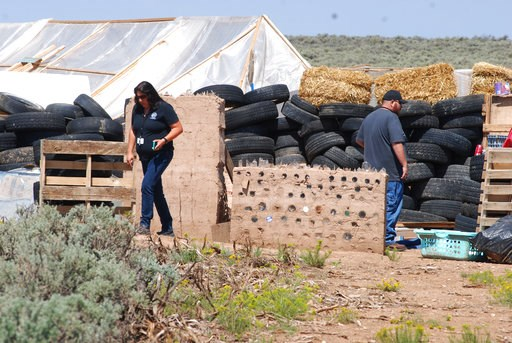 (AP Photo/Morgan Lee). CORRECTS BYLINE TO MORGAN LEE INSTEAD OF LEE MORGAN - Taos County Planning Department officials Rachel Romero, left, and Eric Montoya survey property conditions at a disheveled living compound at Amalia, N.M., on Tuesday, Aug. 7,...