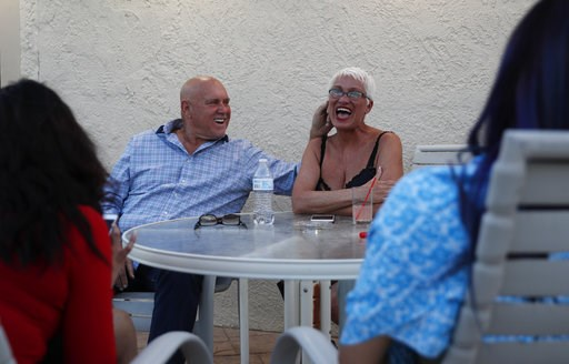 (AP Photo/John Locher, File). FILE - In this April 27, 2018, file photo, owner Dennis Hof, left, jokes with madam Sonja Bandolik at the Love Ranch brothel in Crystal, Nev. County officials in Nevada have yanked a brothel license from the state's most f...