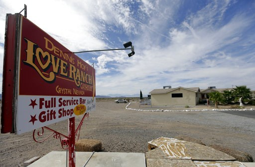 (AP Photo/Chris Carlson, File). FILE - In this Oct. 14, 2015, file photo, a sign advertises Dennis Hof's Love Ranch brothel in Crystal, Nev. County officials in Nevada have yanked a brothel license from the state's most famous pimp who has fashioned hi...