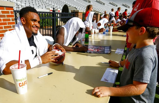 (AP Photo/Butch Dill). Alabama quarterback Jalen Hurts signs an autograph for Brody Bankston after the NCAA college football team's practice, Saturday, Aug. 4, 2018, in Tuscaloosa, Ala.