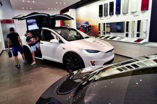 (AP Photo/Richard Vogel). Customers check out the Tesla X, at the Tesla showroom in Santa Monica, Calif., on Wednesday, Aug. 8, 2018. Board members at Tesla are evaluating CEO and Chairman Elon Musk's $72 billion proposal to take the electric car and s...