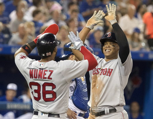 (Fred Thornhill/The Canadian Press via AP). Boston Red Sox'sRafael Devers high-fives with Eduardo Nunez after Devers hit a two-run home run during the sixth inning of a baseball game against the Toronto Blue Jays on Wednesday, Aug. 8, 2018, in Toronto.