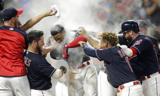 (AP Photo/Tony Dejak). Cleveland Indians' Francisco Lindor, center, is welcomed by teammates after he hit a walk-off three-run home run against the Minnesota Twins in a baseball game Wednesday, Aug. 8, 2018, in Cleveland. The Indians won 5-2.