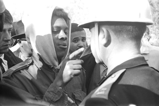 (James Peppler/Alabama Department of Archives and History via AP). This photo provided by Alabama Department of Archives and History, from January 1966 shows Simuel Schutz Jr. speaking to a police officer during a protest following the shooting of a bl...