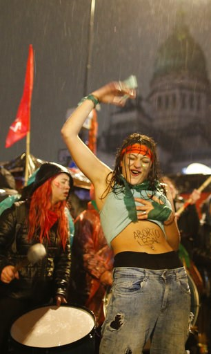 "(AP Photo/Natacha Pisarenko). A women in support of decriminalizing abortion shows the Spanish message ""Legal abortion"" on her stomach as she gathers with others in the rain outside Congress where lawmakers are debating the issue, in Buenos Aires, Arge..."