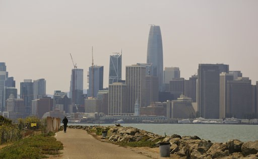 (AP Photo/Lorin Eleni Gill). A man rides a scooter on Treasure Island as the San Francisco city skyline sits in a smoky haze in the background Wednesday, Aug. 8, 2018. Ongoing wildfires in Northern California have worsened air quality in cities miles a...