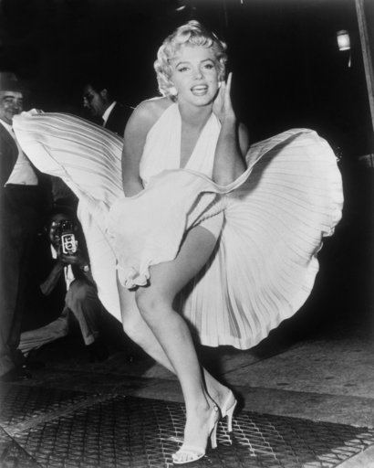 "(AP Photo/Matty Zimmerman). FILE - In this Sept. 9, 1954 file photo, Marilyn Monroe poses over the updraft of a New York subway grate while filming ""The Seven Year Itch"" New York. The dress, created by Bill Travilla, is one of several items that will b..."