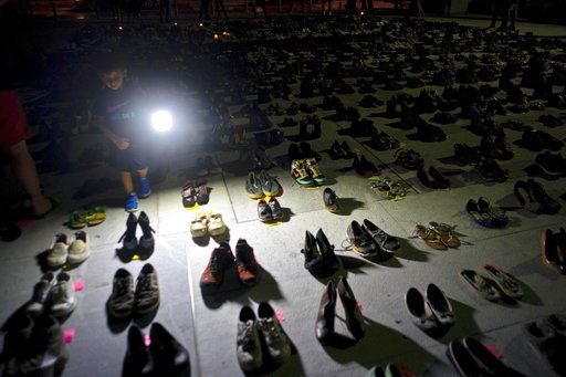 (AP Photo/Ramon Espinosa, File). FILE - In this June 1, 2018 file photo, a child shines a light on hundreds of shoes at a memorial for those killed by Hurricane Maria, in front of the Puerto Rico Capitol in San Juan. Puerto Rico has conceded that Hurri...