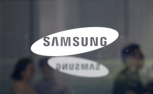 (AP Photo/Ahn Young-joon, File). FILE- In this July 31, 2018, file photo employees walk past logos of the Samsung Electronics Co. at its office in Seoul, South Korea. Samsung is expected to unveil a new phone on Thursday, Aug. 9, 2018.