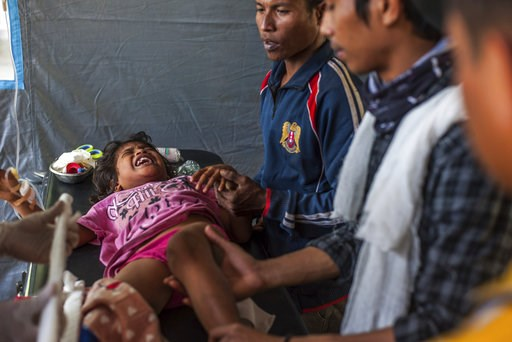 (AP Photo/Fauzy Chaniago). An Indonesian girl who was injured in Sunday's earthquake screams in pain as she is being treated at a makeshift hospital in Kayangan, North Lombok, Indonesia, Thursday, Aug. 9, 2018. Four days after the quake killed a large ...