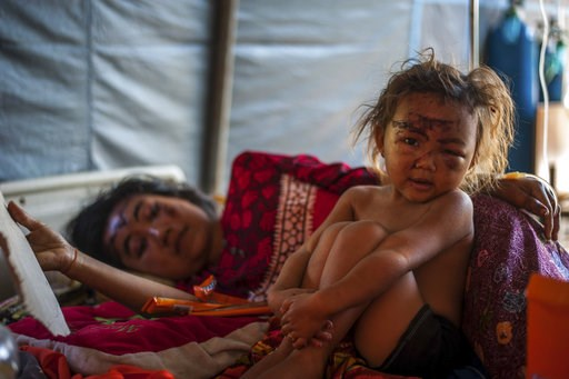 (AP Photo/Fauzy Chaniago). In this photo taken on Wednesday, Aug. 8, 2018, a woung girl and her mother who were injured in Sunday's earthquake rest on a bed at a makeshift hospital in Kayangan, North Lombok, Indonesia. Four days after the quake killed ...