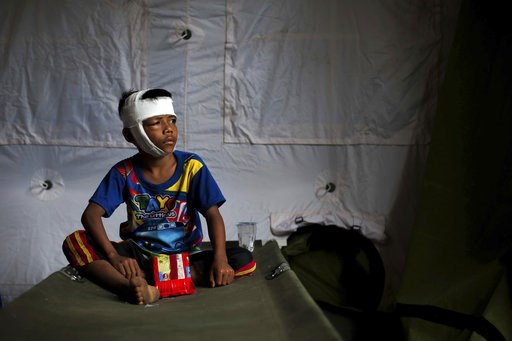 (AP Photo/Fauzy Chaniago). In this photo taken on Wednesday, Aug. 8, 2018, a boy who was injured in Sunday's earthquake sits on a folding bed at a makeshift hospital in Kayangan, North Lombok, Indonesia. Four days after the quake killed a large number ...