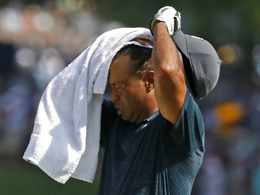 (AP Photo/Brynn Anderson). Tiger Woods wipes sweat from his face on the 17th hole during the first round of the PGA Championship golf tournament at Bellerive Country Club, Thursday, Aug. 9, 2018, in St. Louis.