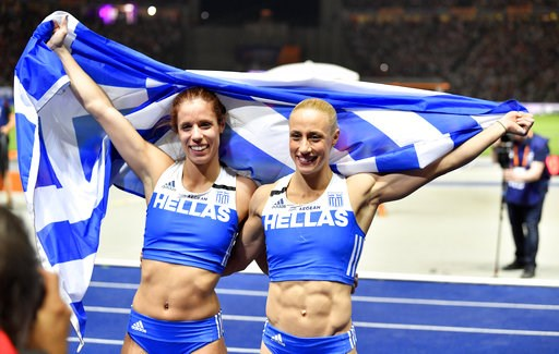 (AP Photo/Martin Meissner). Greece's gold medal winner Ekatarini Stefanidi and silver medal winner Nikoleta Kiriakopoulou celebrate with the Greek flag after the women's pole vault final at the European Athletics Championships at the Olympic stadium in...