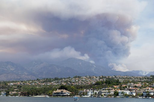 "(Kevin Sullivan/The Orange County Register via AP). A boat floats on Lake Mission Viejo as the ""Holy Fire"" burns in the mountains behind Mission Viejo, Calif., on Wednesday, Aug. 8, 2018."