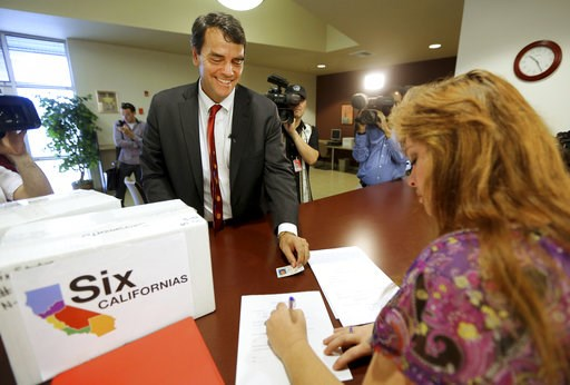 (AP Photo/Rich Pedroncelli, File). FILE - In this July 15, 2014 file photo, Silicon Valley venture capitalist Tim Draper presents his drivers license for identification purposes to Heather Ditty, elections manager for the Sacramento County Registrar of...