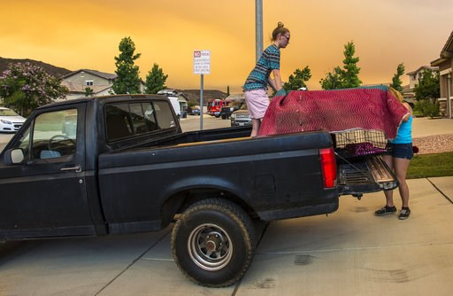 (Mark Rightmire/The Orange County Register via AP). Residents along Crystal Ridge Court in Lake Elsinore, Calif., load a truck as they evacuate as the Holy Fire burns near their home on Wednesday, Aug. 8, 2018.
