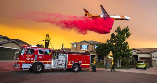 (Mark Rightmire/The Orange County Register via AP). A plane drops fire retardant behind homes along McVicker Canyon Park Road in Lake Elsinore, Calif., as the Holy Fire burned near homes on Wednesday, Aug. 8, 2018.