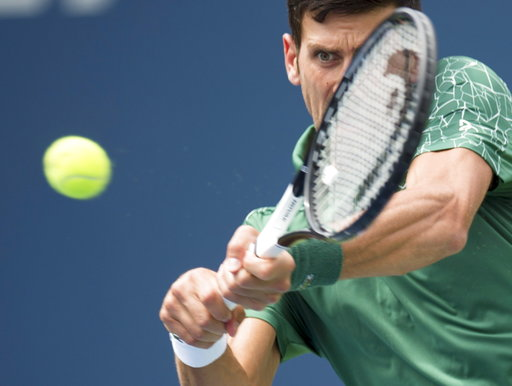 (Frank Gunn/The Canadian Press via AP). Novak Djokovic, of Serbia, makes a return to Stefanos Tsitsipas, of Greece, during the Rogers Cup men's tennis tournament in Toronto, Thursday, Aug. 9, 2018.