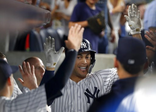 (AP Photo/Julie Jacobson). New York Yankees' Giancarlo Stanton celebrates with teammates after hitting a solo home run against the Texas Rangers during the fifth inning of a baseball game, Thursday, Aug. 9, 2018, in New York.
