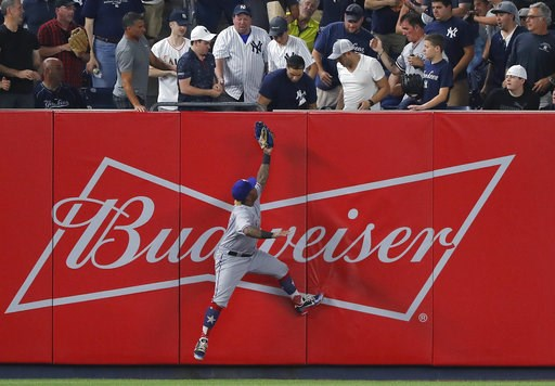 (AP Photo/Julie Jacobson). Texas Rangers left fielder Willie Calhoun (5) cannot make the play on a solo home run by New York Yankees' Neil Walker during the sixth inning of a baseball game, Thursday, Aug. 9, 2018, in New York.