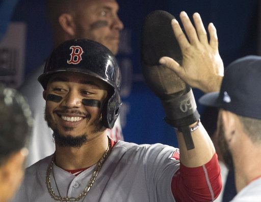 (Fred Thornhill/The Canadian Press via AP). Boston Red Sox's Mookie Betts is congratulated in the dugout after scoring against the Toronto Blue Jays during the first inning of a baseball game Thursday, Aug. 9, 2018, in Toronto.