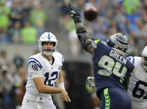 (AP Photo/Stephen Brashear). Indianapolis Colts quarterback Andrew Luck (12) passes through the defense of Seattle Seahawks defensive end Rasheem Green during the first half of an NFL football preseason game, Thursday, Aug. 9, 2018, in Seattle.