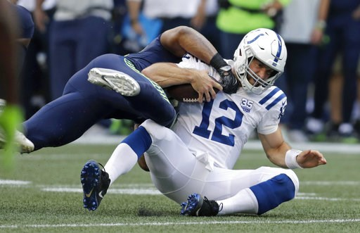 (AP Photo/Stephen Brashear). Indianapolis Colts quarterback Andrew Luck (12) is tackled by Seattle Seahawks linebacker Bobby Wagner during the first half of an NFL football preseason game, Thursday, Aug. 9, 2018, in Seattle.